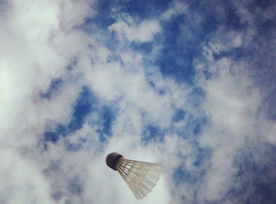 Badmintonboll mot blå himmel med moln